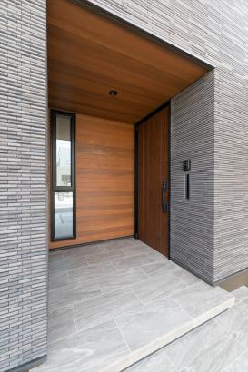 外装のタイルと対照的に、玄関ポーチは本物の杉板を用いて穏やかな印象に。