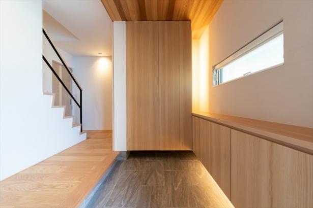 板張り天井と間接照明の優しい光が迎えてくれるエントランス。玄関収納は造作家具です。