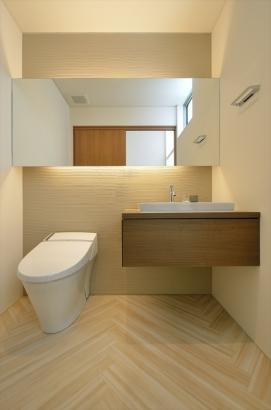造作によるワイドな鏡と吊り洗面台がモダンな印象を与えます。