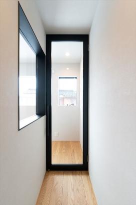 階段を上った先には、冷暖房効率を高めるために仕切り戸を。ガラスを組み込んだ鋼製建具にすることで、廊下も明るくオシャレな空間に。