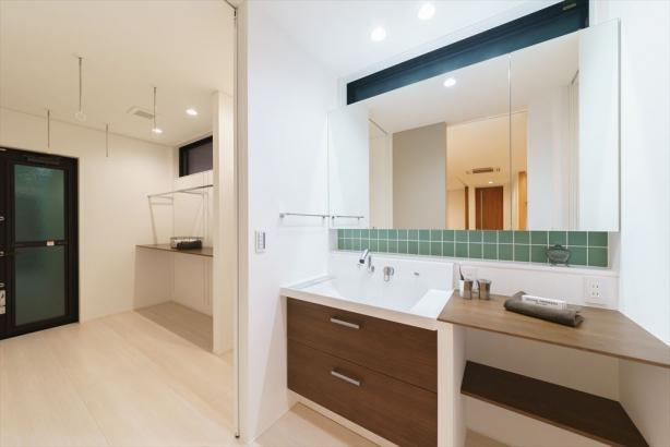 鏡や収納棚を造作した洗面室。ミントグリーンのタイルが、コーディネートのアクセントに。
