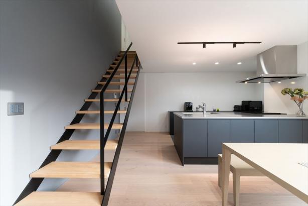 デザイン性の高い鋼製階段をリビングに。キッチンの質感、彩度を抑えた配色も合わさって、非日常的な空間に。
