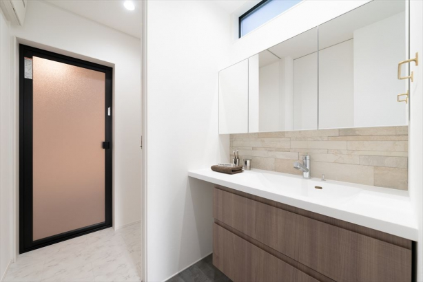 造作による収納や大きな鏡を施した、ラグジュアリーな洗面室。