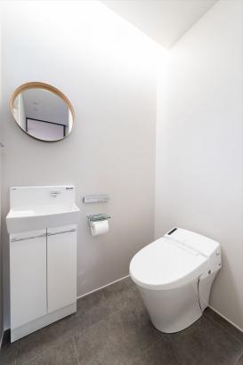 丸い鏡や間接照明など、細部が繊細で上品な印象を与えるトイレ。