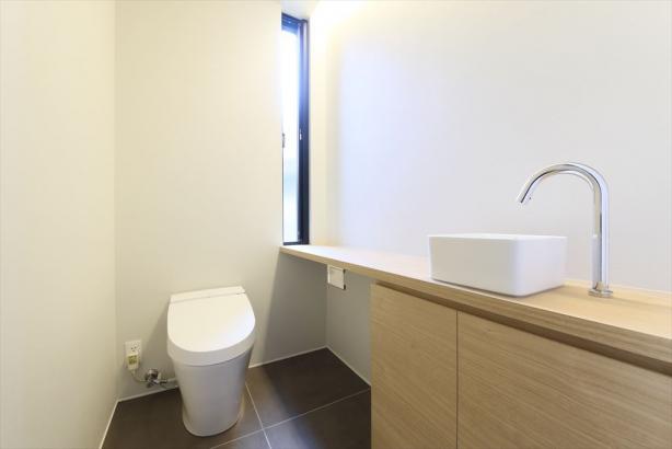 シンプルな手洗い器と造作収納を備えた、清潔感のあるトイレ。