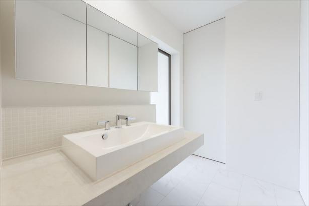 壁面のタイル、洗面ボウル、洗面台に施したモールテックスをホワイトでまとめた清潔感たっぷりの洗面室。