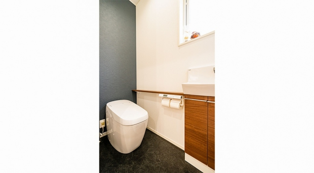 白と黒のコントラストに木のぬくもりが加わったトイレ
