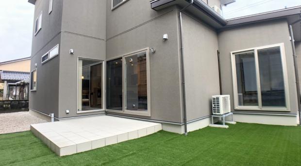 シンプルな外壁に緑が映える、テラスと庭の空間デザイン