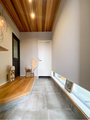 玄関収納へと土間が続くアプローチ。こだわりの建具や木天井で特別感を