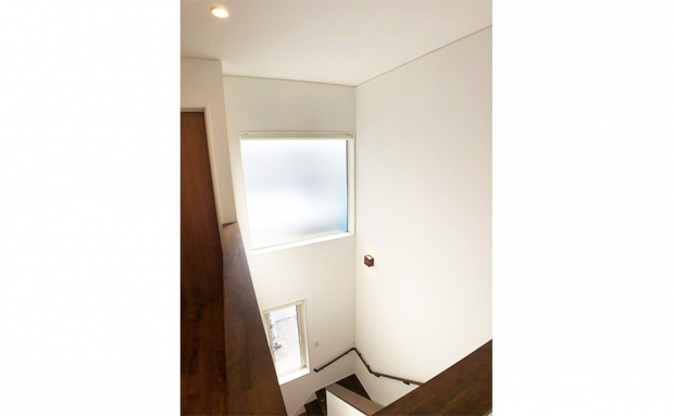 吹抜けの階段には大きな窓。自然光が階段全体を柔らかく照らす