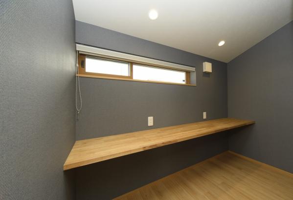 書斎は小さめの窓に落ち着いた色の壁。