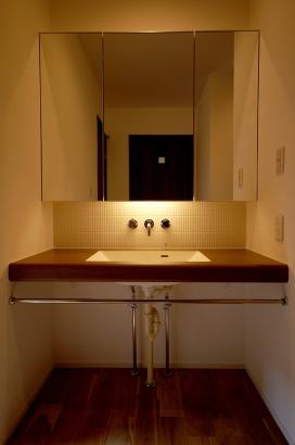鏡の後ろに間接照明を組み込み、上品な空間に。